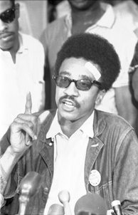 A young African-American man. He is speaking into a microphone, and gesturing; he wears sunglasses.