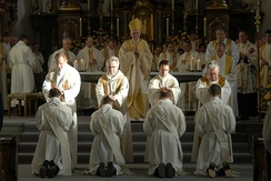 Priests lay their hands on the ordinands during the rite of ordination.