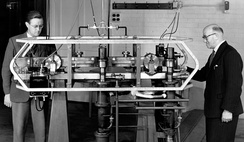 Louis Essen (right) and Jack Parry (left) standing next to the world's first caesium-133 atomic clock.