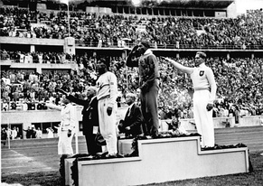 Owens salutes the American flag after winning the long jump at the 1936 Summer Olympics. Naoto Tajima, Owens, Lutz Long.