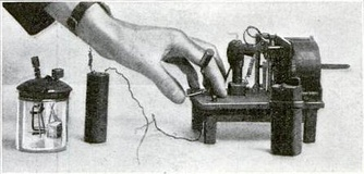 Hughes wireless apparatus, a clockwork driven spark transmitter and battery (right) and a modified version of his carbon block microphone (left) which he used in his 1879 experiments.