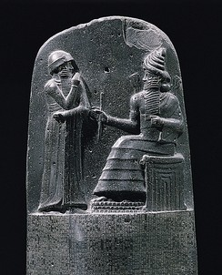 King Hammurabi is revealed the code of laws by the Mesopotamian sun god Shamash, also revered as the god of justice.