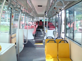 Interior of a wheelchair-accessible transit bus, with bucket seats and smart-card readers at the exit.