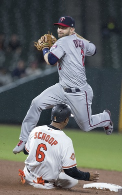 Brian Dozier of the Minnesota Twins leaps over a sliding Jonathan Schoop of the Baltimore Orioles attempting to turn a double play