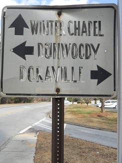 A Dunwoody directional sign indicating Dunwoody Village, Winters Chapel, and Doraville