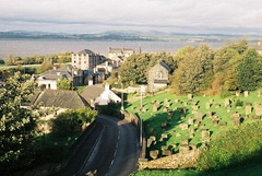 A view of Bo'ness from a hill with a cemetery on the right, houses on the left and the Firth of Forth and Fife in the distance