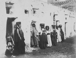 Muslim Ouled Nail girls waiting in the streets of an Algerian village to earn dowry as dancers. Algerian patrons invited them at cafés and festivals or to shrines of Muslim awliya. When their dowries were adequate they returned to their mountain villages and married within the tribe. This centuries-old tradition has continued into modern Algeria. (Photo from the late 19th century, courtesy of Tropenmuseum, The Netherlands)[142]