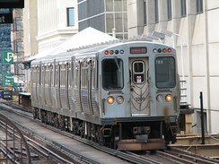 A 4-car train of 3200-series cars pulls into State/Lake