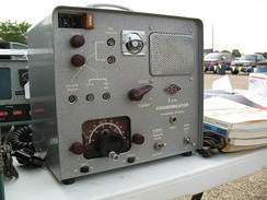 "A Gonset Communicator II 6-meter AM transceiver. This vacuum tube radio with a magic eye tube tuning indicator, was affectionately known as a ""Gooney Box"" and was popular in the 1950s and 60s. A 2-meter version was also sold."