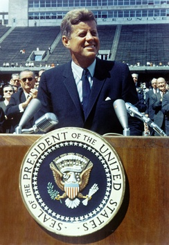 Kennedy, in a blue suit and tie, speaks at a wooden podium bearing the seal of the President of the United States. Vice President Lyndon Johnson and other dignitaries stand behind him.