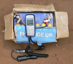 Information and communication technologies for development help to fight poverty. A mobile phone being charged from a car battery in Uganda.