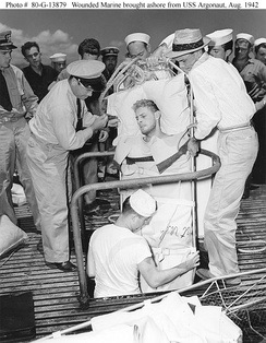 A Marine Raider, injured during the Makin operation, is lifted through a hatch on USS Argonaut to be taken ashore at Pearl Harbor, 26 August 1942.