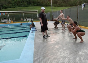 Swimmers perform squats as warm-up exercise prior to entering the pool in a U.S. military base, 2011