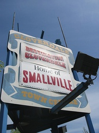 "A white billboard with a blue ribbon around the edges. On the ribbon, ""Cloverdale Town Centre"" appear in yellow surrounding two banners. The top banner reads, ""Destination Cloverdale"" and the bottom reads, ""Home of Smallville""."