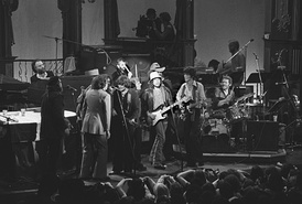 A black and white photo of about a dozen musicians performing on a stage.