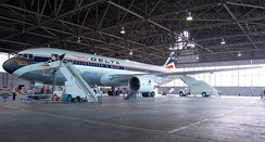 Side view of a parked Delta Air Lines twin-engine jet in hangar, with stairs mounted next to the aircraft's forward door