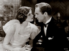 Hepburn and David Manners acting in A Bill of Divorcement. They are holding hands and looking at each other emotionally.