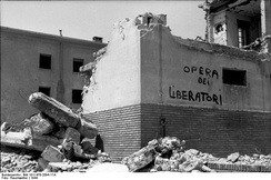 "Propaganda inscription, ""the work of the liberators"" (opera dei liberatori) on wall of a bombed building, Rome, 1944"