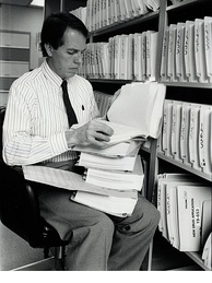 Medical Officer Alexander Fleming, M. D., examines a portion of a 240-volume new drug application around the late 1980s. Applications grew considerably after the efficacy mandate under the 1962 Drug Amendments.