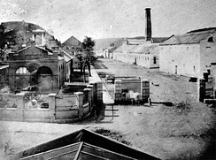 "1862 photograph of the Harpers Ferry arsenal; the ""engine house"" (John Brown's Fort) is on the left."