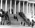 Body bearers carrying the casket of President Kennedy up the center steps of the United States Capitol Building, followed by a color guard holding the flag of the President of the United States, and the late President's widow, Jacqueline Kennedy and her children, Caroline Kennedy and John F. Kennedy, Jr., on November 24, 1963.
