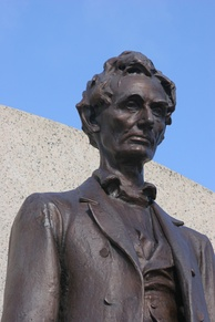 The upper portion of a large outdoor metal statue of Abraham Lincoln, beardless and thoughtful