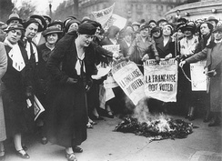 "Louise Weiss along with other Parisian suffragettes in 1935. The newspaper headline reads ""The Frenchwoman Must Vote."""