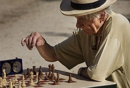 An older adult human male European in Paris – playing chess at the Jardins du Luxembourg.