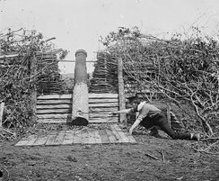 "Quaker gun near Centreville, Virginia, in March 1862, after the Confederate withdrawal; a man with a stick is pretending to ""fire"" it with a linstock"