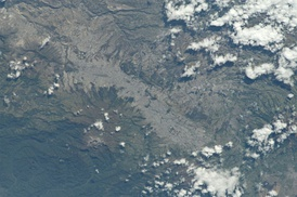 View of Quito from the International Space Station (north is at the left of the image). Quito sits on the eastern slopes of the Pichincha Volcano, whose crater is visible.