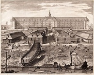 The shipyard of the United East India Company (VOC) in Amsterdam (1726 engraving by Joseph Mulder). The shipbuilding district of Zaan, near Amsterdam, became one of the world's earliest known industrialized areas, with around 900 wind-powered sawmills at the end of the 17th century. By the early seventeenth century Dutch shipyards were producing a large number of ships to a standard design, allowing extensive division of labour, a specialization which further reduced unit costs.[198]