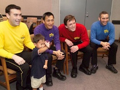 Four of the original Wiggles (and a fan) in 2004 (seated from left to right: Greg Page, Jeff Fatt, Murray Cook, and Anthony Field)