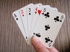 A hand of playing cards, ace through five.