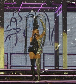 "Minogue singing ""All the Lovers"", as confetti falls down upon her, during 2014's Kiss Me Once Tour."
