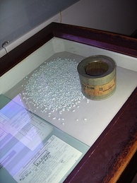 "A can of Zyklon B with adsorbent granules and original signed documents detailing ordering of Zyklon B as ""materials for Jewish resettlement"" (on display at Auschwitz concentration camp museum)"