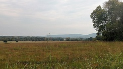 The Lower Boston Mountains (background) rise from the flat, grassy Springfield Plateau at Prairie Grove Battlefield State Park in Prairie Grove