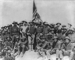 Colonel Roosevelt and the Rough Riders after capturing Kettle Hill along with members of the 3rd Volunteers and the regular Army black 10th Cavalry