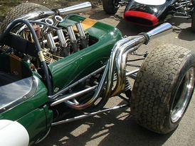 Close-up of rear of a green racing car, showing the engine, exhausts, rear suspension and rear wheels