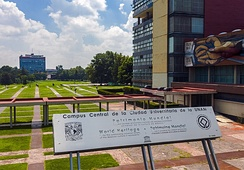 "A silvery metal sign on supports leaning away from the camera saying ""World Heritage Site"" in Spanish and English, with supporting text. Behind it is a building with a mural, a covered walkway, and a large quad with buildings in the distance"