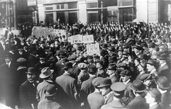 Black and white photograph of a large crowd of people, a few holding signs above the crowd, displaying IWW acronyms and slogans.