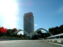 A photo showing the Malaysian Parliament building along with 2 white arches in diagonal position front of the building.