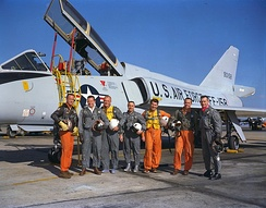 The Mercury Seven stand in front of an F-106B