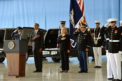 Obama and Clinton at a somber occasion, honoring the Benghazi attack victims at the Transfer of Remains Ceremony, held at Andrews Air Force Base on September 14, 2012. Soldiers are standing behind Obama and Clinton, and everyone is standing on a large wooden floor with their left hands to their side and their right hands on their upper chests.