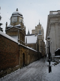 Senate House Passage in the snow with Senate House on the right and Gonville and Caius College on the left.