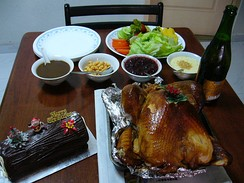 A roast turkey surrounded by Christmas log cake, gravy, sparkling juice, and vegetables