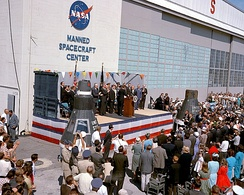 Dignitaries on an outdoor stage in front of a building with NASA Manned Spacecraft Center on the side