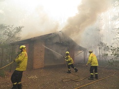 Firefighters work to save a burning house from an out-of-control bushfire in South West Sydney