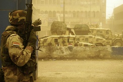 An Iraqi soldier and vehicles from the 42nd Brigade, 11th Iraqi Army Division during a firefight with armed militiamen in the Sadr City district of Baghdad 17 April 2008.