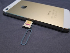 An iPhone 5S with the SIM slot open. The SIM ejector tool is still placed in the eject hole.