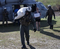 An American soldier delivers aid to a damaged village